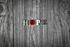 Γκρίζο ξύλινο υπόβαθρο με την ελπίδα λέξης στοκ φωτογραφίες