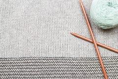 Γκρίζο πλεκτό ύφασμα φιαγμένο από πολύχρωμο νήμα με το πλέξιμο των δικράνων α Στοκ Φωτογραφίες