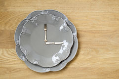 Γκρίζο ρολόι πιάτων σε ένα ξύλινο υπόβαθρο στοκ εικόνες