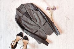 Γκρίζο σακάκι με ένα μανίκι δέρματος, μαύρα παπούτσια, άγρια λουλούδια Μοντέρνη έννοια στην άσπρη γούνα Στοκ φωτογραφία με δικαίωμα ελεύθερης χρήσης