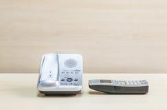 Γκρίζο τηλέφωνο κινηματογραφήσεων σε πρώτο πλάνο, τηλέφωνο γραφείων στο θολωμένο ξύλινο γραφείο και κατασκευασμένο υπόβαθρο τοίχω Στοκ Εικόνες