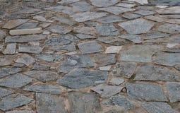 Γκρίζο υπόβαθρο ενός δρόμου φιαγμένου από πέτρες των διαφορετικών μεγεθών κοντά επάνω στοκ φωτογραφίες