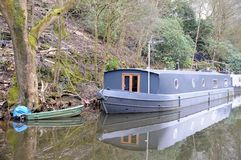 Γκρίζο houseboat φορτηγίδων με την πράσινη βάρκα κωπηλασίας που δένεται σε ένα κανάλι Στοκ εικόνες με δικαίωμα ελεύθερης χρήσης