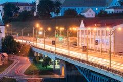Γκρόντνο, Λευκορωσία Κυκλοφορία νύχτας στη γέφυρα πέρα από τον ποταμό Neman στο βράδυ στα φω'τα φωτισμών νύχτας Στοκ Εικόνες