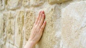 Γλιστρώντας χέρι γυναικών ενάντια στον παλαιό τοίχο πετρών σε σε αργή κίνηση Θηλυκό χέρι σχετικά με την τραχιά επιφάνεια του βράχ φιλμ μικρού μήκους
