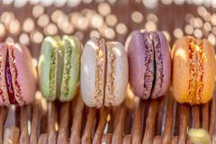 Γλυκά γαλλικά χρωματισμένα macaroons σε έναν αγροτικό ξύλινο πίνακα Εύγευστα γλυκά για το τσάι στοκ εικόνες