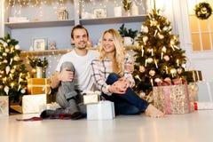 Γλυκά δώρα Χριστουγέννων ανοίγματος ζευγών στοκ φωτογραφία