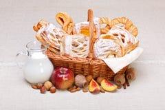 Γλυκά κέικ στη διακόσμηση καλαθιών, καρπού και γάλακτος στοκ εικόνα
