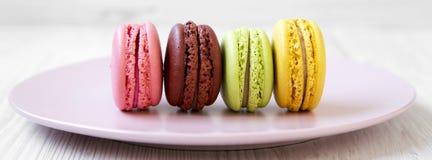 Γλυκά και ζωηρόχρωμα macaroons στο ρόδινο πιάτο σε μια άσπρη ξύλινη επιφάνεια, πλάγια όψη closeup στοκ εικόνες