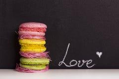 Γλυκά macaroons και υπόβαθρο πινάκων κιμωλίας με το κείμενο αγάπης Στοκ εικόνα με δικαίωμα ελεύθερης χρήσης