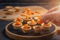 Γλυκά tartlets μαγειρέματος με τις φέτες tangerine και της σοκολάτας - να ξετυλίξει tangerine φέτες στοκ εικόνα