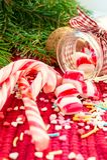 Γλυκές καραμέλες που ανατρέπονται/που χύνονται από το βάζο γυαλιού στο backgro Χριστουγέννων Στοκ Εικόνες