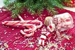 Γλυκές καραμέλες που ανατρέπονται/που χύνονται από το βάζο γυαλιού Πράσινα Χριστούγεννα έλατου Στοκ φωτογραφία με δικαίωμα ελεύθερης χρήσης