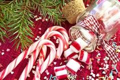 Γλυκές καραμέλες που ανατρέπονται/που χύνονται από το βάζο γυαλιού Πράσινα Χριστούγεννα έλατου Στοκ Εικόνες