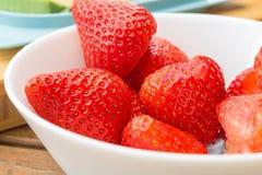 Γλυκές κόκκινες φράουλες, που εξυπηρετούνται σε ένα άσπρο κεραμικό κύπελλο ώριμος και γλυκός Στοκ Εικόνα