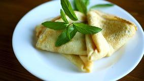 Γλυκές λεπτές τηγανίτες με τη μαρμελάδα σε ένα πιάτο φιλμ μικρού μήκους