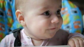 Γλυκιά συνεδρίαση μωρών και χασμουρητό cheerily καθμένος σε μια καρέκλα σε σε αργή κίνηση απόθεμα βίντεο