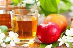 Γλυκοί χυμός μήλων, μήλα και λουλούδια στον πίνακα Στοκ εικόνες με δικαίωμα ελεύθερης χρήσης