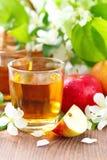 Γλυκοί χυμός μήλων, μήλα και λουλούδια στον πίνακα Στοκ Φωτογραφίες