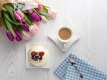 Γλυκό κέικ με τα λουλούδια καφέ και τουλιπών στον πίνακα στοκ εικόνες