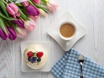 Γλυκό κέικ με τα λουλούδια καφέ και τουλιπών στον πίνακα στοκ φωτογραφία