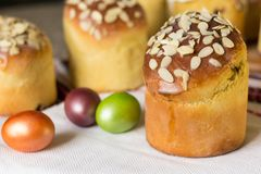 Γλυκό κέικ Πάσχας kulich που ολοκληρώνεται με τις νιφάδες αμυγδάλων με τα χρωματισμένα αυγά r στοκ εικόνα με δικαίωμα ελεύθερης χρήσης