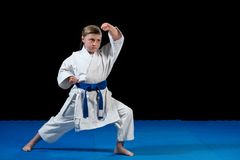 Γλυκό μικρό κορίτσι στην πρακτική πολεμικών τεχνών όπως karate το παιδί μόνο που απομονώνεται στο μαύρο υπόβαθρο στοκ εικόνες