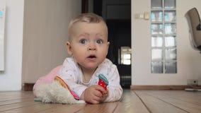 Γλυκό μπλε-eyed κοριτσάκι με το παιχνίδι στο πάτωμα στο σπίτι απόθεμα βίντεο