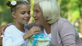 Γλυκό παιδί που δίνει το χριστουγεννιάτικο δώρο στην παλαιά γιαγιά της, εορτασμός στην οικογένεια απόθεμα βίντεο