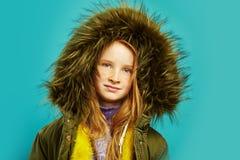 Γλυκό παιδί στο σακάκι φθινοπώρου με τη μεγάλη κουκούλα γουνών σε πράσινο στοκ φωτογραφίες με δικαίωμα ελεύθερης χρήσης