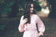 Γλυκό brunette με τις μπούκλες σε ένα φόρεμα στοκ φωτογραφία με δικαίωμα ελεύθερης χρήσης
