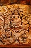 Γλυπτικές των Θεών πέρα από μια πόρτα banteay ναός srei της Καμπότζης angkor Στοκ Φωτογραφίες