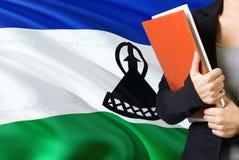Γλωσσική έννοια εκμάθησης Νέα γυναίκα που στέκεται με τη σημαία του Λεσόθο στο υπόβαθρο Βιβλία εκμετάλλευσης δασκάλων, πορτοκαλί  στοκ εικόνα