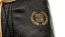 Γνήσιο ασφαλίστρου διακριτικό σημαδιών δέρματος χειροποίητο στα εγκιβωτίζοντας γάντια Στοκ Εικόνες