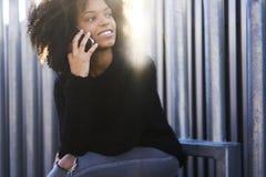Γοητεία της εύθυμης γυναίκας αφροαμερικάνων που χρησιμοποιεί την ασύρματη σύνδεση σε Διαδίκτυο Στοκ Εικόνες