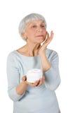 Γοητεία της ηλικιωμένης γυναίκας που εφαρμόζει την καλλυντική κρέμα στο πρόσωπό της για την του προσώπου φροντίδα δέρματος σε ένα στοκ εικόνες