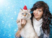 Γοητεία της νέας γυναίκας με τη γάτα στο santa ΚΑΠ στοκ εικόνα