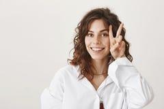 Γοητεία της νέας γυναίκας με τη χαριτωμένη σγουρή τρίχα που παρουσιάζει χειρονομία ειρήνης ή νίκης κοντά στο πρόσωπο χαμογελώντας στοκ φωτογραφίες