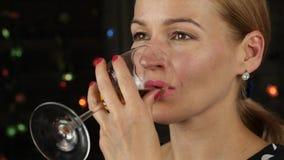 Γοητεία της νέας γυναίκας που πίνει το άσπρο κρασί σε ένα σκοτάδι όμορφη κυρία κινηματογραφήσεων σε πρώτο πλάνο με το ποτήρι του  φιλμ μικρού μήκους