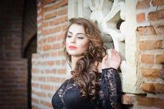 Γοητεία της νέας γυναίκας brunette στη μαύρη μπλούζα δαντελλών κοντά σε έναν τούβλινο τοίχο. Προκλητική πανέμορφη νέα γυναίκα με τ Στοκ εικόνα με δικαίωμα ελεύθερης χρήσης