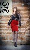 Γοητεία της νέας γυναίκας brunette στη μαύρη μπλούζα δαντελλών, την κόκκινη φούστα και τα υψηλά τακούνια κοντά στο τουβλότοιχο. Πρ Στοκ εικόνες με δικαίωμα ελεύθερης χρήσης