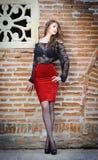 Γοητεία της νέας γυναίκας brunette στη μαύρη μπλούζα δαντελλών, την κόκκινη φούστα και τα υψηλά τακούνια κοντά στο τουβλότοιχο. Πρ Στοκ Εικόνες