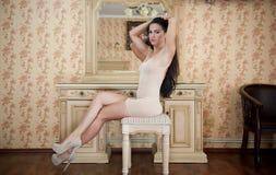 Γοητεία της νέας γυναίκας brunette στο σφιχτό κατάλληλο κοντό nude φόρεμα μπροστά από έναν καθρέφτη Προκλητικό πανέμορφο μακρυμάλ Στοκ φωτογραφία με δικαίωμα ελεύθερης χρήσης