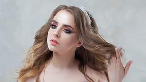Γοητεία της νέας νύφης με την πολυτέλεια hairstyle Η όμορφη γυναίκα αγγίζει την τρίχα Hairstyle με τις χνουδωτές μπούκλες στοκ εικόνες με δικαίωμα ελεύθερης χρήσης