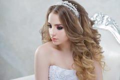 Γοητεία της νέας νύφης με την πολυτέλεια hairstyle Όμορφη γυναίκα στη συνεδρίαση γαμήλιων φορεμάτων σε μια καρέκλα στοκ φωτογραφίες με δικαίωμα ελεύθερης χρήσης