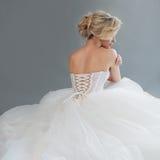 Γοητεία της νέας νύφης στο πολυτελές γαμήλιο φόρεμα κορίτσι αρκετά λευκό Γκρίζα ανασκόπηση μπακαράδων στοκ εικόνες