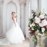 Γοητεία της νέας νύφης στο πολυτελές γαμήλιο φόρεμα Το όμορφο κορίτσι, είναι κοντά στο μεγάλο παράθυρο στοκ εικόνες