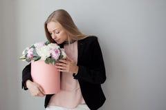 Γοητεία της ξανθής γυναίκας με τα λουλούδια σε ένα κιβώτιο καπέλων Ανθοδέσμη των peonies Το κορίτσι στο επιχειρησιακό ύφος, λαμβά στοκ φωτογραφίες με δικαίωμα ελεύθερης χρήσης