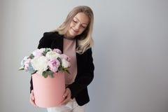 Γοητεία της ξανθής γυναίκας με τα λουλούδια σε ένα κιβώτιο καπέλων Ανθοδέσμη των peonies Το κορίτσι στο επιχειρησιακό ύφος, λαμβά στοκ εικόνες με δικαίωμα ελεύθερης χρήσης