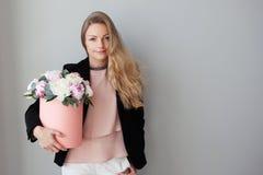 Γοητεία της ξανθής γυναίκας με τα λουλούδια σε ένα κιβώτιο καπέλων Ανθοδέσμη των peonies Το κορίτσι στο επιχειρησιακό ύφος, λαμβά στοκ εικόνες